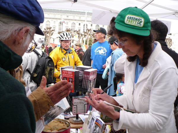 Image of Carol Brouillet with cookies at the Northern California 9/11 Truth Alliance booth