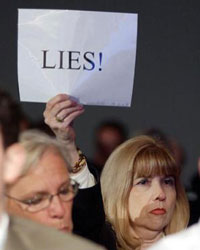 Image of Sally Regenhard, member of september 11th families, holding sign at Commission hearing reading: LIES!