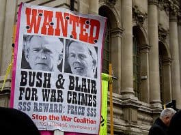 Image of protestor holding sign that reads: WANTED Bush & Blair for War Crimes