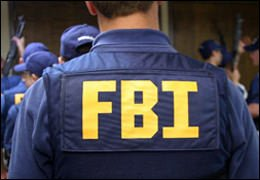 FBI agent viewed from behind wearing an FBI vest