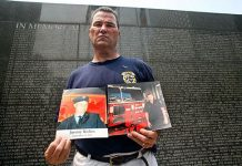 Photo of foremer FDNY Chief Jim Riches holding a photo of his son Jimmy
