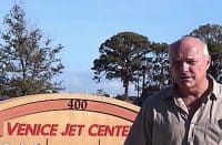 Daniel Hopsicker in front of the sign for the Venice Jet Center