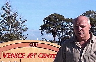 Daniel Hopsicker in front of the sign for the Venice Jet Center, Venice Florida