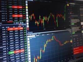 A monitor displays financial data and charts