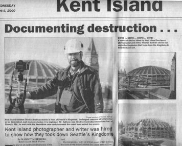 Photo of newspaper article documenting destruction with an image of Thomas Sullivan in front of Seattle's Kingdome, the largest sructure razed by controlled demolition
