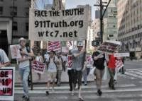 People protesting in NYC, marching in the street with a banner that reads, face the truth, 9-11 truth.org