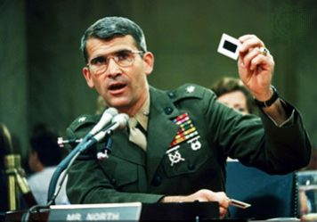 Image of Oliver North testifying before Congress, holding a slide in his hand