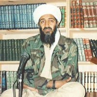 Osama bin Laden sitting inside his Tora Bora hideout in front of Islamic books to videotape a message.