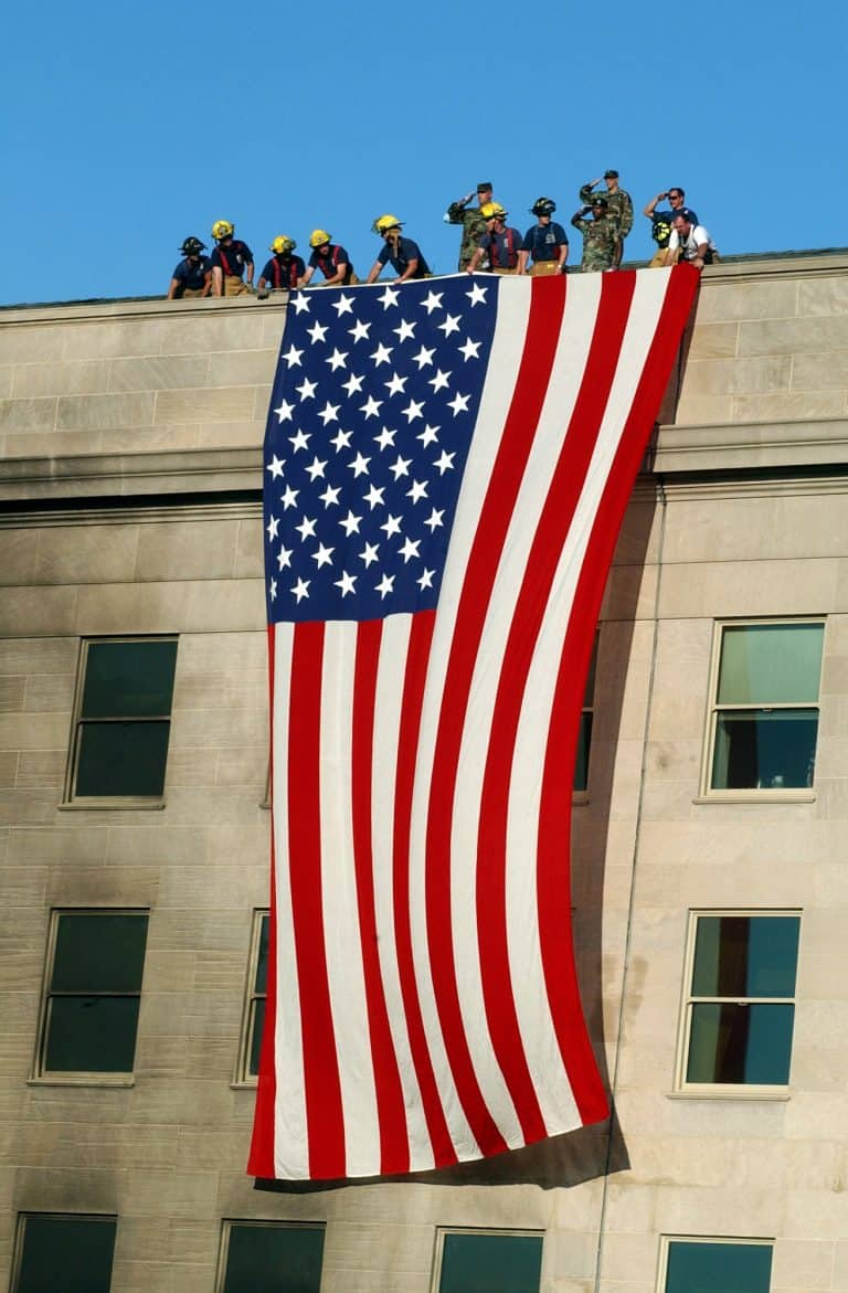 Military servicemembers render honors as fire and rescue workers unfurl a huge American flag over the side of the Pentagon during rescue and recovery efforts following the 11 Sept. terrorist attack.