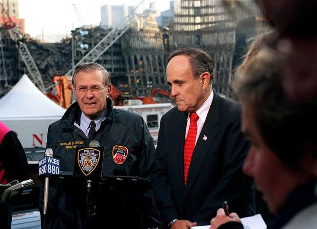 Giuliani and Rumsfeld at Ground Zero giving a radio interview with mic in front of Donald Rumsfeld