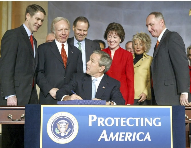 Photo of United States President, George W.Bush signing the Intelligence Reform Bill into law surrounded by members of Congress