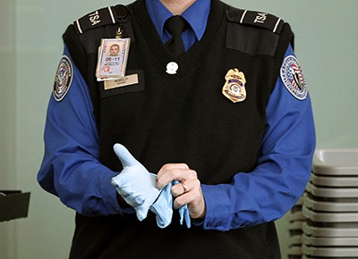 Photo of A TSA agent's hands as he puts on rubber gloves at Washington Reagan National Airport