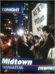 Midtown Manhattan at night with scene of people demonstrating at the opening of United 93