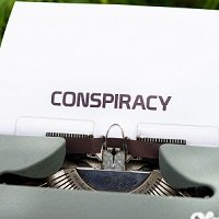 Conspiracy typed out on a sheet of paper sticking out of a typewriter