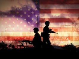 Armed soldier's silhouettes stand out against an American flag