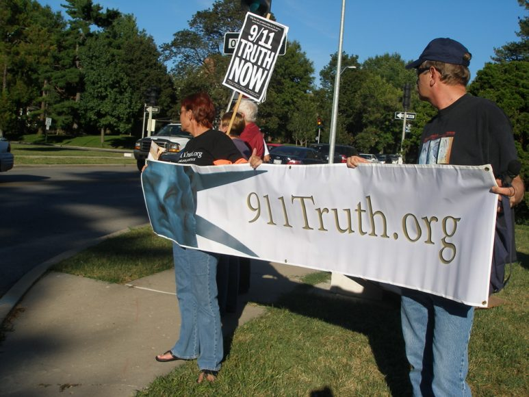 Kansas City Missouri, a group of people hold a banner with 911Truth.Org in large letters.