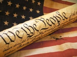An image of the Constitution as a scroll floats above the American Flag