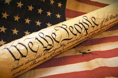 An image of the first line of the preamble to the US Constitution on a scroll that rests on a worn looking flag