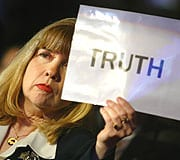 Sally Regenhard holds up sign with the word TRUTH