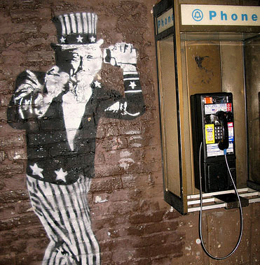 Uncle sam, rendered in graffiti on brick wall, next to a payphone wiretapping your calls
