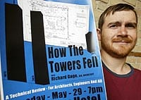 Photo of Joe Hawkins holding a poster of the how the towers fell